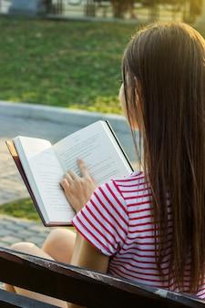 Hintere ansicht einer jungen frau, die ein buch liest und im park sich entspannt