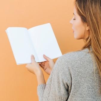 Hintere ansicht einer jungen frau, die in der hand weißbuch gegen pfirsichhintergrund hält