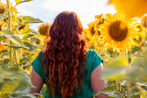 Hintere ansicht einer jungen frau mit rotem lockigem haar und einem grünen kleid, das in einem sonnenblumenfeld aufwirft