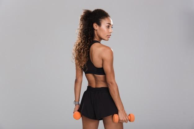 Hintere ansicht einer selbstbewussten jungen afrikanischen sportlerin, die übungen mit hanteln lokalisiert über grauem hintergrund tut