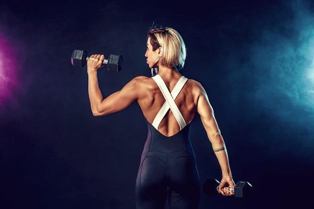 Hintere ansicht einer sportlichen frau in der modernen sportkleidung tut die übungen mit dummköpfen. foto der muskulösen frau auf dunkler wand mit rauche. kraft und motivation.