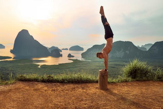 Hintere ansicht einer yogahaltung. glücklicher mann in der schwarzen kleidung, welche die yogahaltung steht auf seinen händen auf dem baum tut.