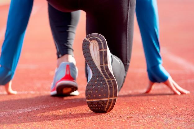Hintere ansicht eines athleten, der zum rennen auf einer laufbahn fertig wird. konzentrieren sie sich auf den schuh eines athleten, der kurz davor ist, ein rennen im stadion zu starten.
