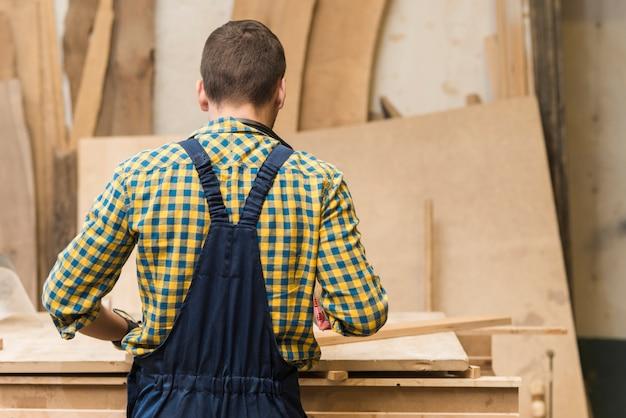 Hintere ansicht eines heimwerkers, der in der werkstatt arbeitet