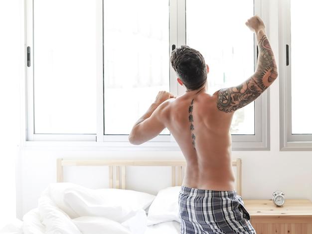Hintere ansicht eines hemdlosen jungen mannes, der auf bett im schlafzimmer ausdehnt