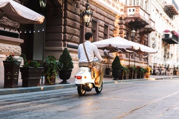 Hintere ansicht eines jungen geschäftsmannes, der auf einem motorrad draußen auf einer stadtstraße reitet