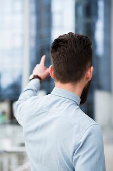 Hintere ansicht eines jungen geschäftsmannes, der finger zeigt