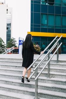 Hintere ansicht eines kletternden treppenhauses der geschäftsfrau