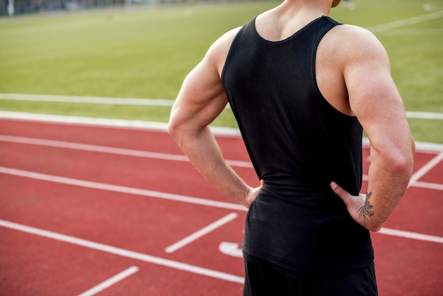 Hintere ansicht eines männlichen athleten mit den händen auf der hüfte, die auf rennstrecke steht