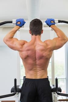 Hintere ansicht eines männlichen bodybuilders, der zug tut, ups an der turnhalle