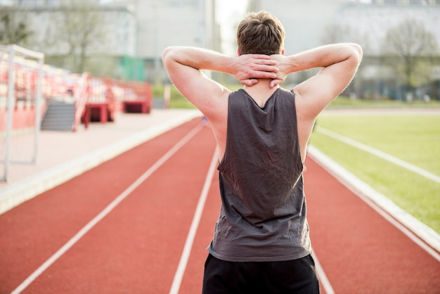 Hintere ansicht eines männlichen läufers, der auf rennstrecke mit ihren händen hinter seinem kopf steht