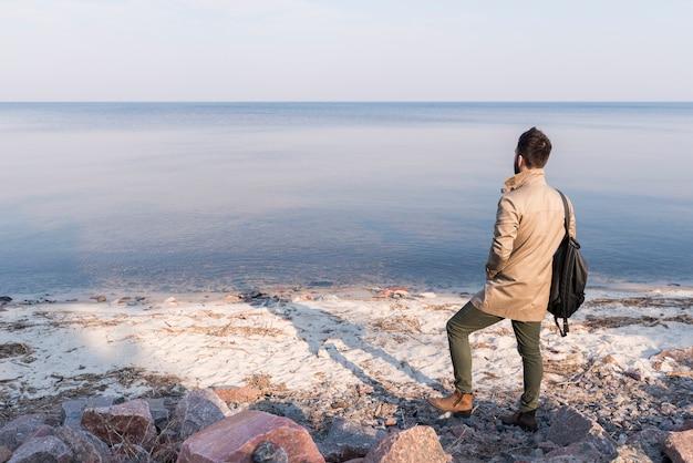 Hintere ansicht eines männlichen reisenden, der ruhigen meerblick betrachtet