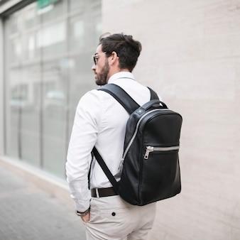 Hintere ansicht eines männlichen touristen mit schwarzem rucksack