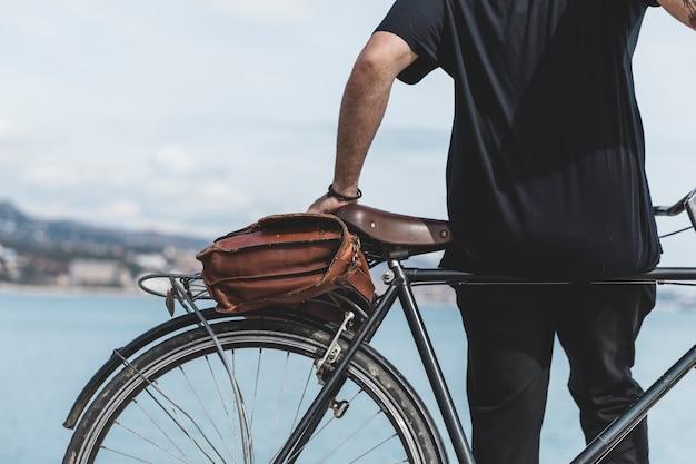 Hintere ansicht eines mannes, der auf fahrrad nahe der küste sich lehnt