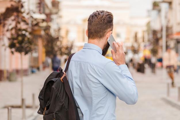 Hintere ansicht eines mannes, der auf mobiltelefon spricht