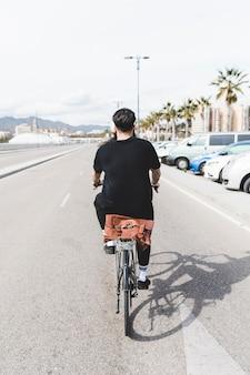Hintere ansicht eines mannes, der fahrrad auf gerade straße fährt