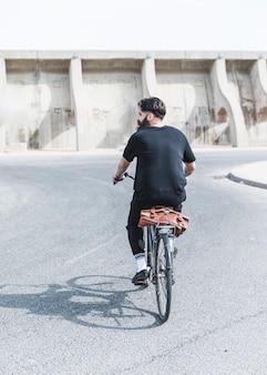 Hintere ansicht eines mannes, der fahrrad auf straße fährt