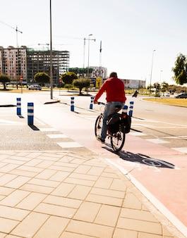 Hintere ansicht eines mannes, der fahrrad auf straße in der stadt fährt