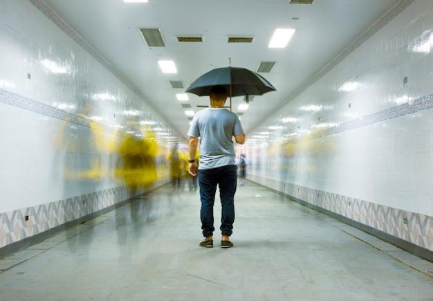 Hintere ansicht eines mannes, der regenschirm mit langer belichtungstechnik der unscharfen leute hält