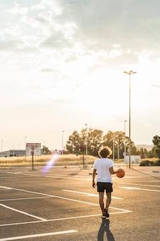 Hintere ansicht eines mannes, der vor gericht basketball spielt