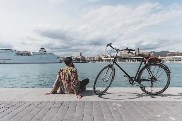 Hintere ansicht eines mannes mit dem fahrrad, das nahe bucht sitzt