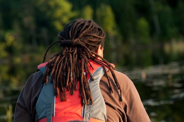 Hintere ansicht eines mannes mit den dreadlocks, die eine schwimmweste in see des holzes, ontario tragen