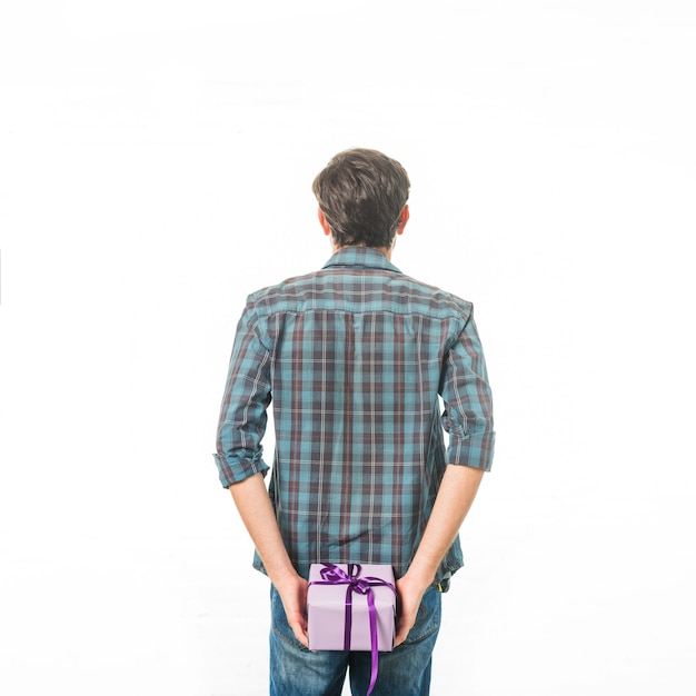 Hintere ansicht eines mannes mit der geschenkbox, die auf weißem hintergrund steht