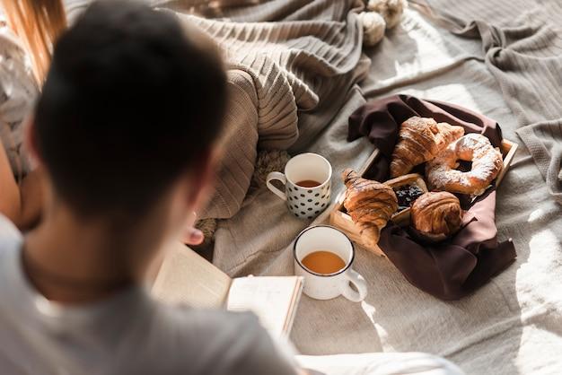 Hintere ansicht eines mannlesebuches mit frühstück auf bett