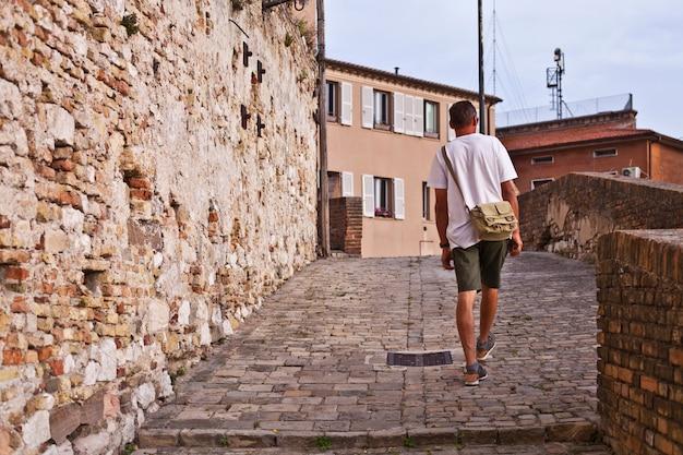 Hintere ansicht eines manntouristen, der in alte stadt geht