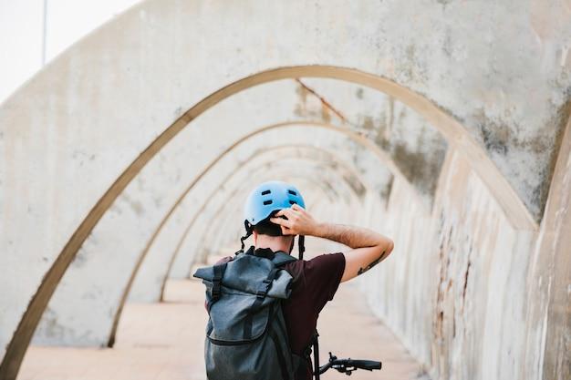 Hintere ansicht eines radfahrers, der auf seinen sturzhelm sich setzt