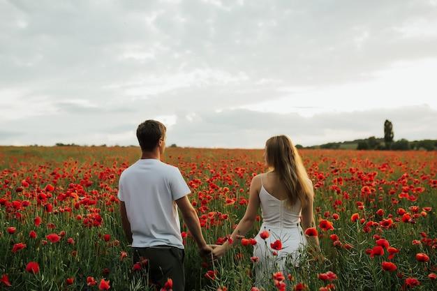 Hintere ansicht eines romantischen paares in den weißen kleidern, die hände in einem feld mit roten blumen halten