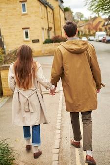 Hintere ansicht eines schattenbildes eines liebevollen paares, gehend entlang die alte straße der englischen stadt