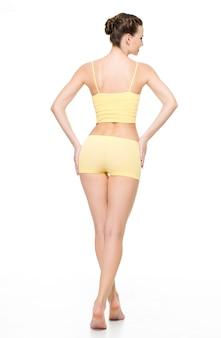 Hintere ansicht eines schönen sportlichen weiblichen körpers in der gelben unterwäsche, die auf weißer wand lokalisiert aufwirft