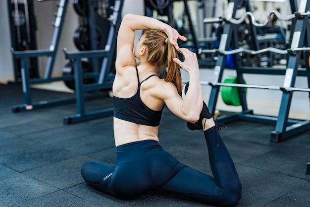 Hintere ansicht eines sportlichen trainers in der zufälligen spitze und in den gamaschen, die auf dem boden in der haltung beim ausdehnen ihres körpers in der turnhalle sitzen