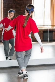 Hintere ansicht eines tanzens der jungen frau vor spiegel