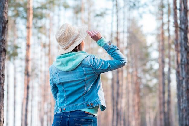 Hintere ansicht eines tragenden hutes der frau auf dem kopf, der bäume im wald betrachtet