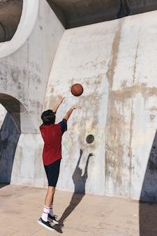 Hintere ansicht eines übenden basketballs des teenagers