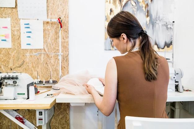 Hintere ansicht eines weiblichen designers, der im shop arbeitet