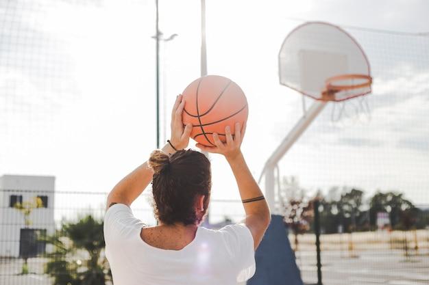 Hintere ansicht eines werfenden basketballs des mannes vor gericht