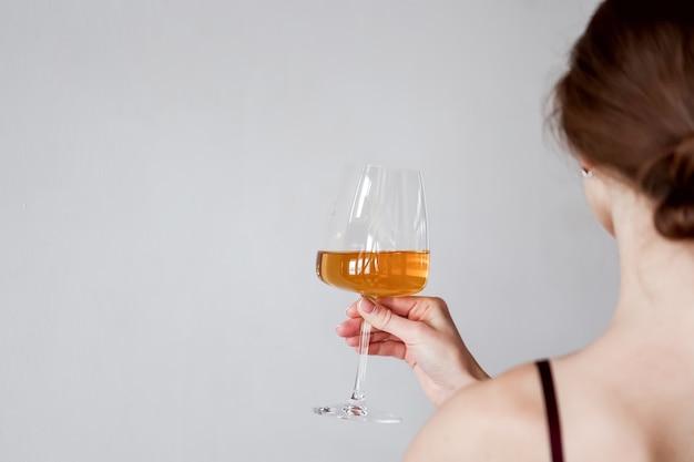 Hintere ansicht junge frau, die ein glas weißwein hält und schmeckt