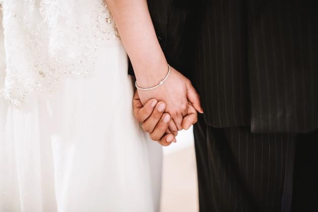 Hintere ansicht-mittelteil der braut und des bräutigams, die hand halten