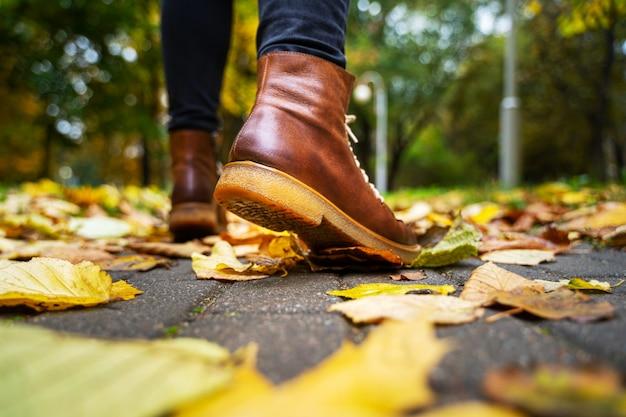 Hintere ansicht über die füße einer frau in den schwarzen hosen und in den braunen stiefeln gehend in einen park entlang dem bürgersteig, der mit gefallenen blättern gestreut wird.