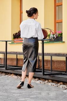 Hintere ansicht von dame im lederrock und im weißen hemd nahe der tabelle auf der straße mit lederhandtasche