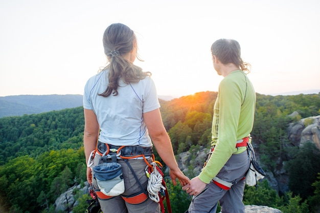Hintere ansicht von den bergsteigern, die auf dem gebirgsgipfel stehen