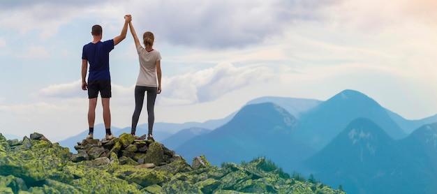 Hintere ansicht von den jungen touristischen paaren, von athletischem mann und von dünnem mädchen, die mit dem händchenhalten der angehobenen arme auf felsigem berg stehen.