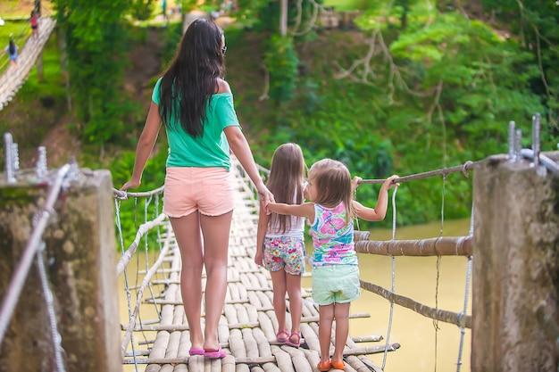 Hintere ansicht von den kleinen mädchen und von junger frau, die auf hängebrücke über dem fluss loboc, philippinen gehen