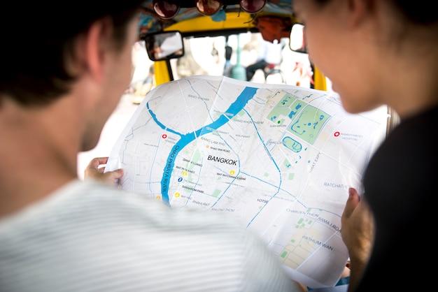 Hintere ansicht von den leuten, die unter verwendung karte bangkoks thailand überprüfen