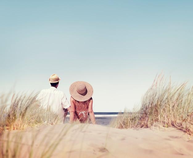 Hintere ansicht von den paaren, die zusammen am strand sitzen