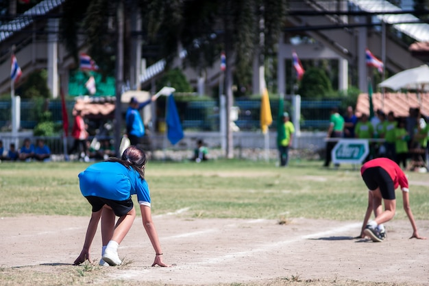 Hintere ansicht von den studentinnen bereit, auf laufbahn an einem sporttag zu laufen