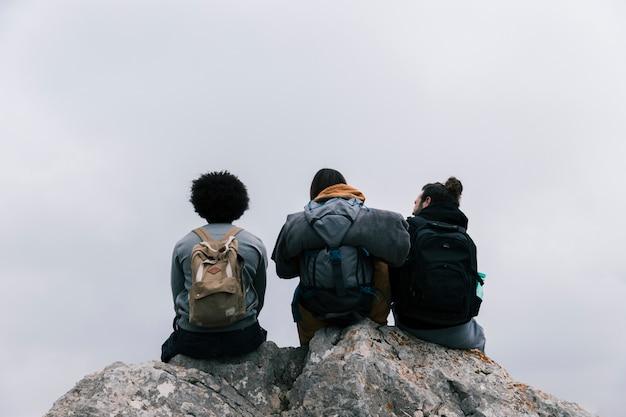 Hintere ansicht von drei freunden, die auf felsen gegen himmel sitzen